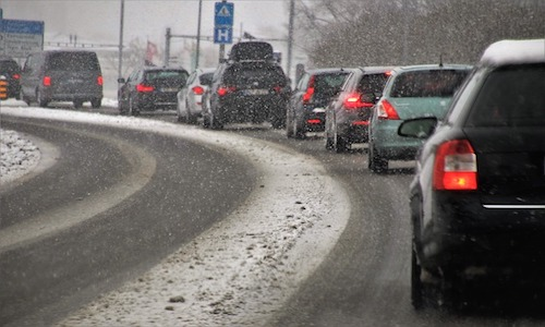 A crowded roadway during a snowstorm.